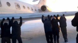 シベリアの氷上で動けなくなった飛行機を乗客が押す