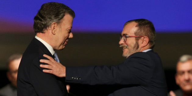 Colombia's President Juan Manuel Santos, left, shakes hands with with Rodrigo Londono, known as Timochenko,...