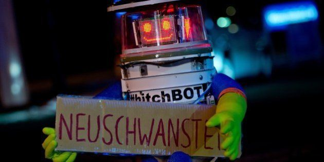 Robot 'hitchBOT' is seen holding a sign reading 'Neuschwanstein' as he waits for a lift at the roadside...