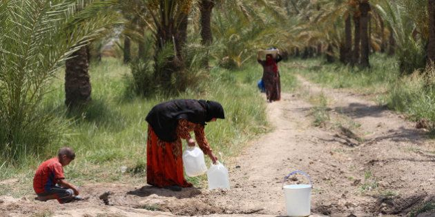 Iraqis displaced by conflict collect water at al-Takia refugee camp in Baghdad, Iraq, Thursday, July...