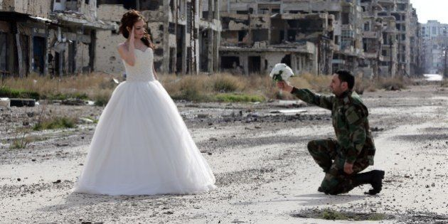 Newly-wed Syrian couple Nada Merhi,18, and Syrian army soldier Hassan Youssef,27, pose for a wedding...
