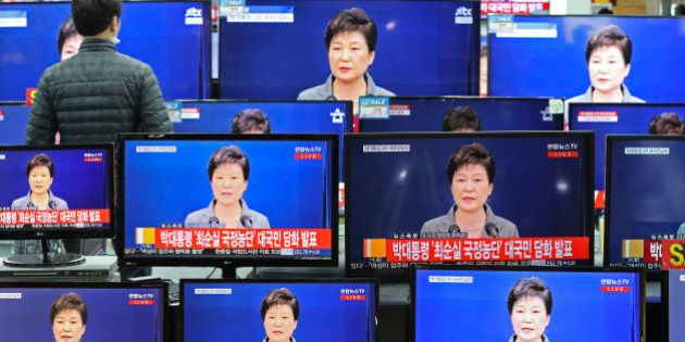 TV screens display the live broadcast of South Korean President Park Geun-hye's public announcement at...
