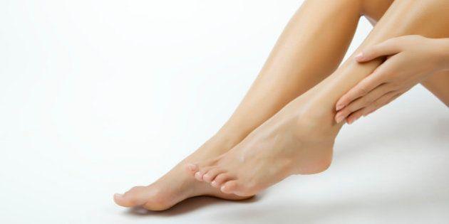 Woman moisturizing legs,