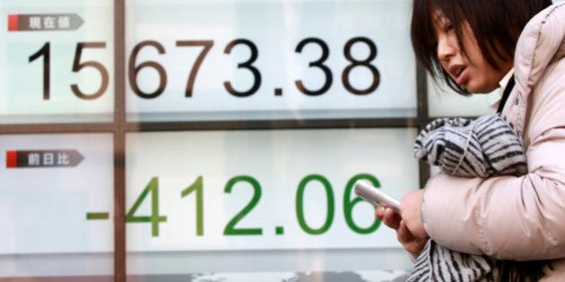A woman walks past an electronic stock board showing Japan's Nikkei 225 in Tokyo, Wednesday, Feb. 10,...