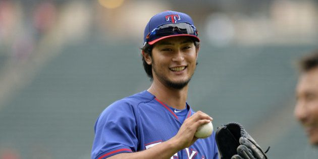 CHICAGO, IL - AUGUST 4: Starting pitcher Yu Darvish #11 of the Texas Rangers smiles as he plays catch...
