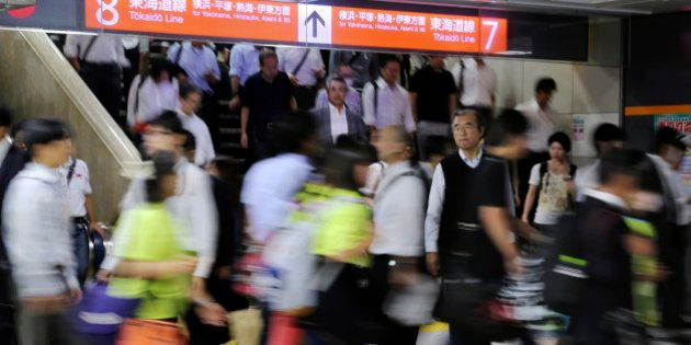 In this Friday, Sept. 12, 2014 photo, commuters walk through a train station during a morning rush hour...
