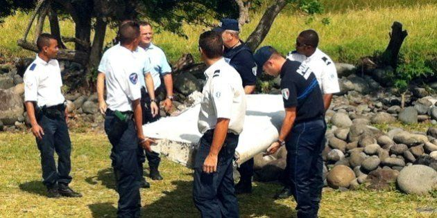 Police and gendarmes carry a piece of debris from an unidentified aircraft found in the coastal area...