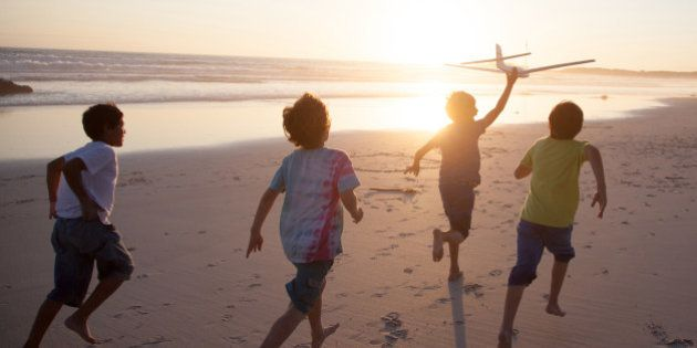 Boys, aged 9-10, running along a beach at sunset with a toy