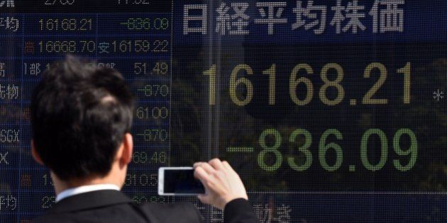 A businessman uses his smartphone to take pictures of an electric quotation board flashing the Nikkei...