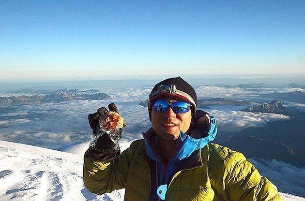 モンブランの山頂でモンブランを持つ松本圭司さん。様々な山に登り、アプリにフィードバックする。