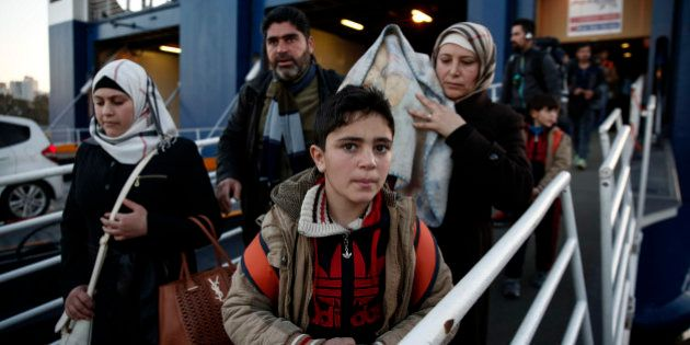 Migrants and refugees disembark from a ferry after their arrival at the port of Piraeus near Athens,...