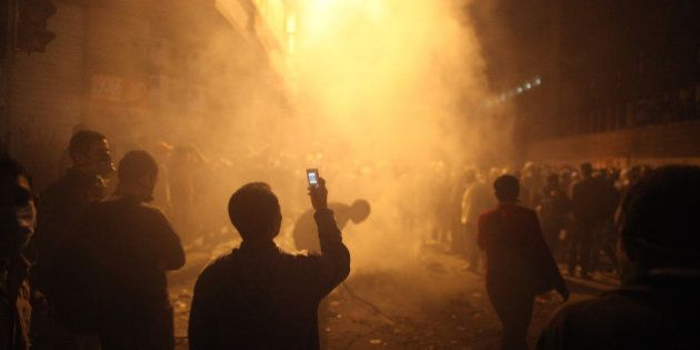 CAIRO, EGYPT - NOVEMBER 23: A youth films the aftermath of a tear gas volley fired by police on protestors...