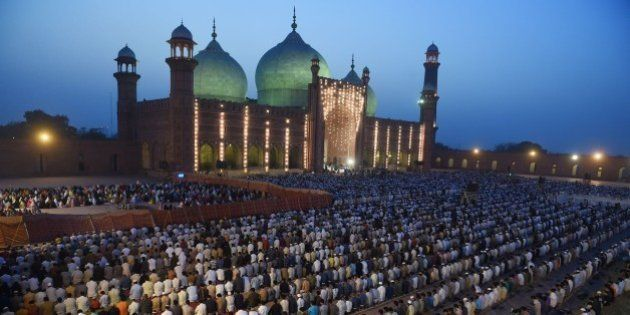 Pakistani worshippers offer evening prayers at the historical Badshahi mosque in Lahore on April 25,...