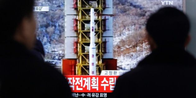 People watch a TV news reporting a rocket launch in North Korea, at Seoul Railway Station in Seoul, Sunday,...