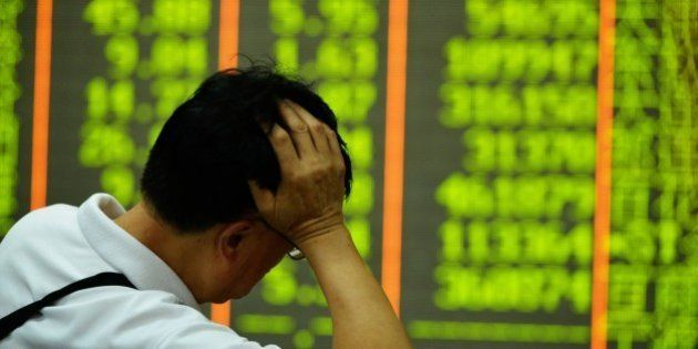 An investor rests on his arm before a screen that shows share prices in a security firm in Hangzhou,...