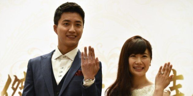 Taiwanese table tennis player Chiang Hung-chieh (L) and his Japanese wife Ai Fukuhara display their wedding...