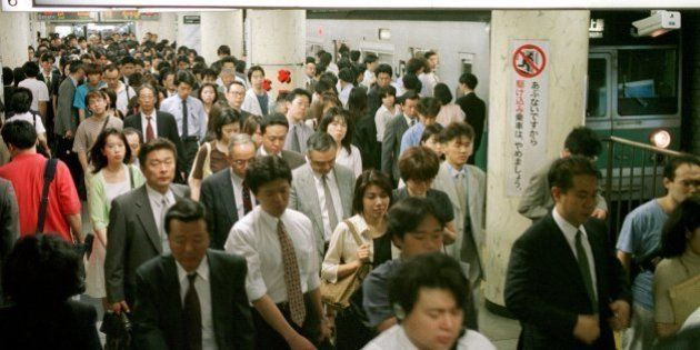 Japanese commuters pack a platform of the Chiyoda-line, one of Tokyo's most popular subway lines, during...
