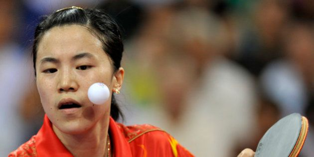 Wang Nan of China plays a shot during her women's team table tennis final match against Feng Tianwei...
