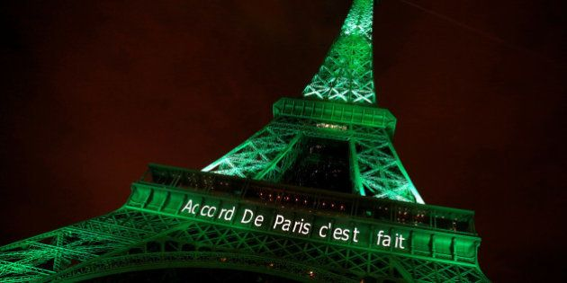 The Eiffel tower is illuminated in green with the