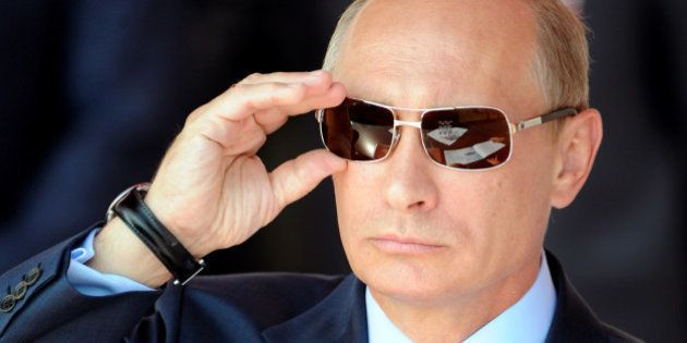 Russian Prime Minister Vladimir Putin adjusts his sunglasses as he watches an air show during MAKS-2011,...