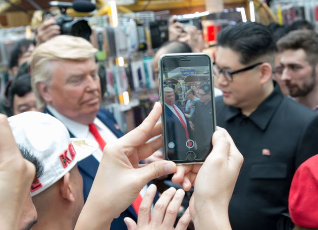 Kim Jong Un and Donald Trump impersonators Howard X (R) and Dennis Alan (L) are surrounded by onlookers...