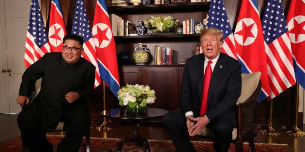 U.S. President Donald Trump sits next to North Korea's leader Kim Jong Un before their bilateral meeting...