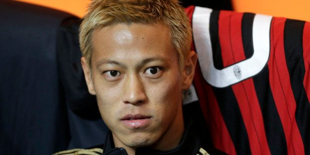 AC Milan's Keisuke Honda looks on as he sits on the bench before the Italian Serie A soccer match against...