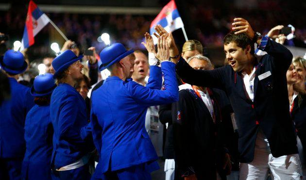 ロンドン五輪では、約7万8000人のボランティアが参加した。閉会式で出場選手とハイタッチをするボランティア参加者(左)。