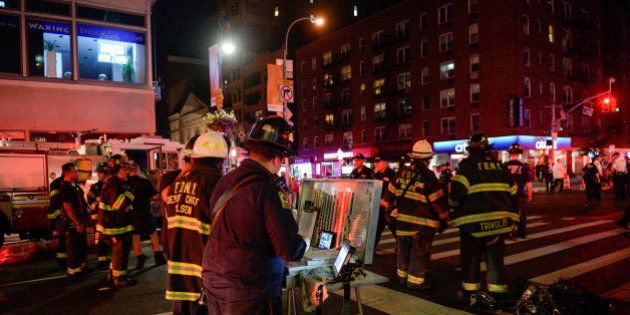 New York City police and firefighters stand near the site of an explosion in the Chelsea neighborhood...