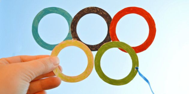 Child is holding a symbol for an Olympics, five Olympic circles made of colorful papers, cut out and...