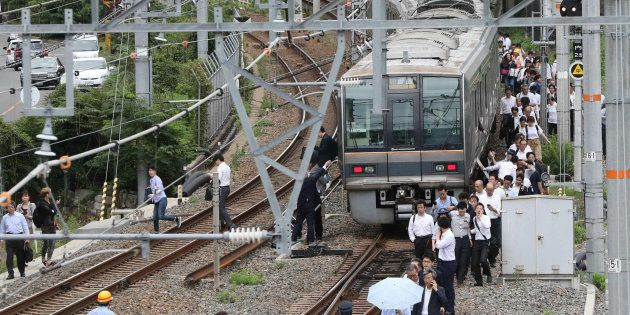 線路を歩いてJR新大阪駅に向かう乗客=18日午前9時4分、大阪市淀川区