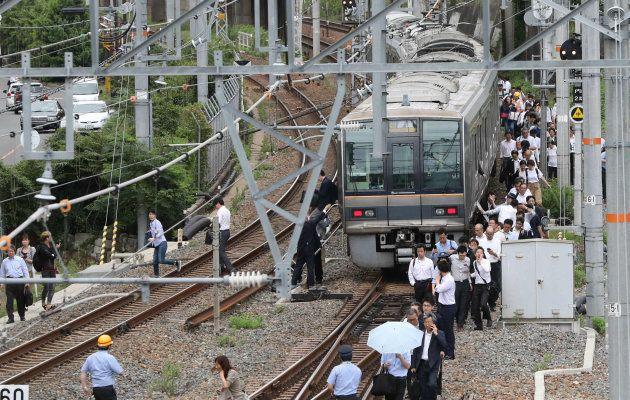 線路を歩いてJR新大阪駅に向かう乗客=18日午前9時4分、大阪市淀川区 撮影日:2018年06月18日