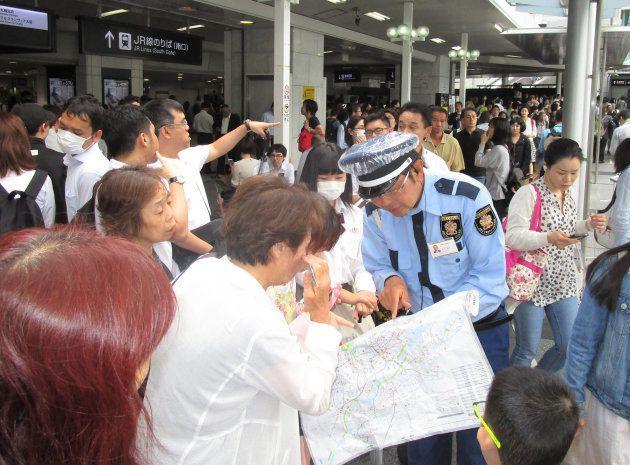 地震の影響で電車が止まり、警備員にバスの行き先を確認する人たち=18日午前9時半すぎ、JR大阪駅前 撮影日:2018年06月18日