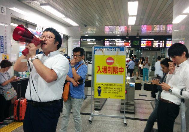 地震で鉄道が運転見合わせになり、安否確認を呼び掛ける駅員(左)=18日午前、JR大阪駅 撮影日:2018年06月18日
