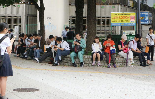 地震発生後、交差点の縁石に座りスマートフォンで安否を確認する人々=18日午前9時ごろ、大阪市中央区 撮影日:2018年06月18日
