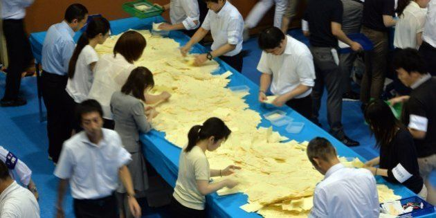 Officers of the election administration committee count ballot papers for Japan's Upper House elections...
