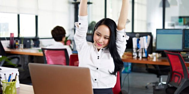 asian businesswoman stretching arms in the air to celebrate completion of