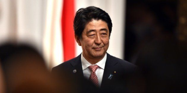 Japanese Prime Minister Shinzo Abe smiles after he delivered a speech at the 50th anniversary ceremony...