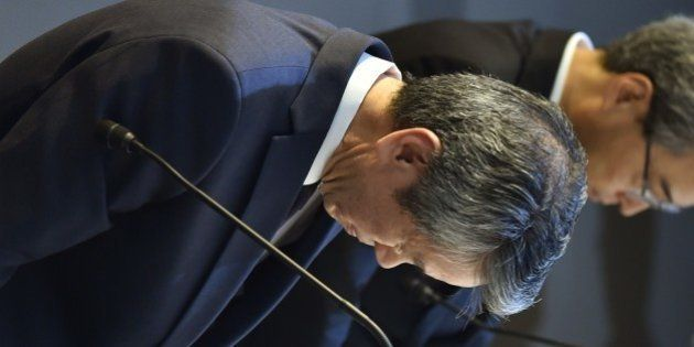 President of Toshiba, Hisao Tanaka (L) bows at the end of a press conference at the company's headquarters...