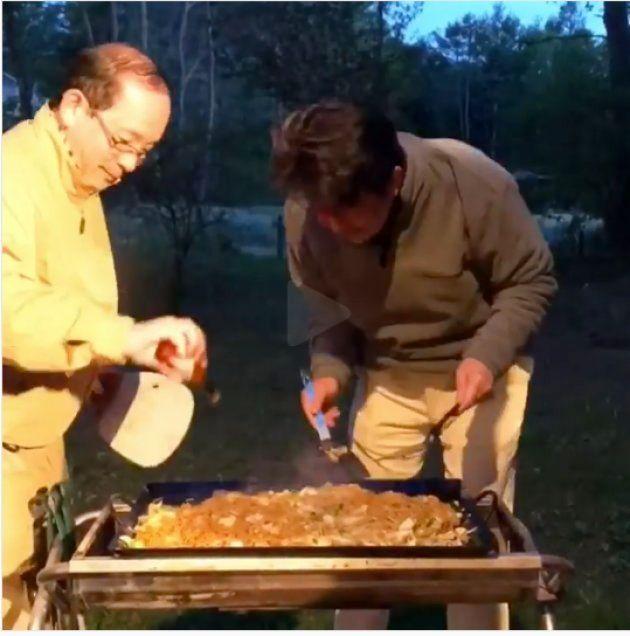 焼きそばを調理する安倍首相。左で調理を手伝う人がタバスコを入れる様子をじっと見ている。