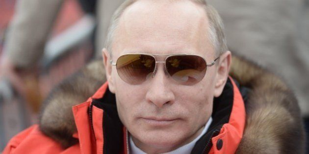 In this photo taken Saturday, March 8, 2014, Russian President Vladimir Putin watches downhill ski competition...