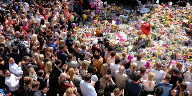 Members of the public attend a minute of silence for the victims of the Manchester Arena attack, in St...