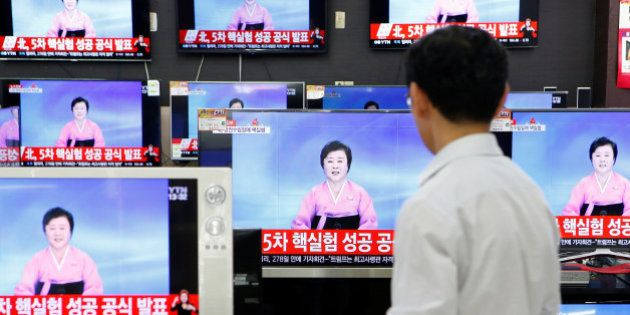 A sales assistant watches TV sets broadcasting a news report on North Korea's fifth nuclear test, in...