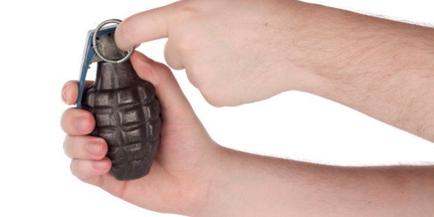 Hands holding grenade pulling the pin.Please also