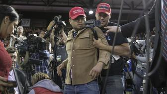 A Trump supporter, center, is restrained after he storms the media area, as journalists including BBC reporter Gary ODonoghue, second left, work during a rally with U.S. President Donald Trump in El Paso, Texas, U.S., on Monday, Feb. 11, 2019. Trump and prospective Democratic challenger Beto O'Rourke took part in dueling rallies in Texas on Monday, with each using the president's proposed border wall as an early proxy for the 2020 election. Photographer: Adria Malcolm/Bloomberg via Getty Images