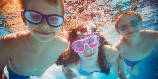 Three kids swimming underwater. Little girl and her brothers having fun in the swimming pool. Focus in...