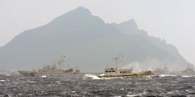 A Taiwan Coast Guard boat (R-with red flag) is blocked by a Japan Coast Guard vessel (L) in the waters...