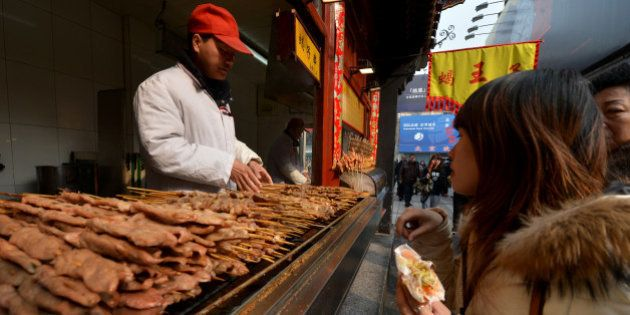 A Chinese hawker barbecues lamb kebabs at his stall in the Wangfujing shopping street of Beijing on February...