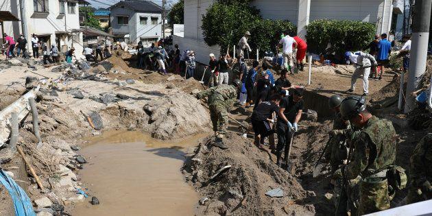 自衛隊員と川底にたまった土砂を取り除く人たち=7月11日、広島市安芸区