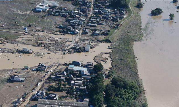 水位が下がり、市街地への水の流れが止まった鬼怒川(右)。中央は決壊した堤防=